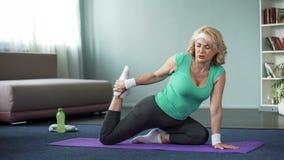 Mulher madura cansada que faz os exercícios da ioga, esticando os pés, estilo de vida saudável imagem de stock