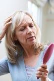 Mulher madura com escova Corncerned sobre a queda de cabelo foto de stock