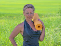 Mulher madura com esteira do exercício imagens de stock