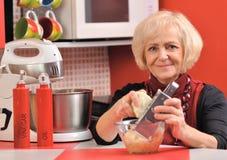 A mulher madura cozinha a refeição na cozinha vermelha. Imagens de Stock