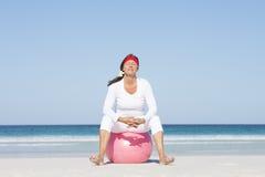 Mulher madura da aposentadoria ativa na praia foto de stock