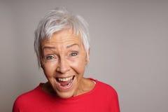 Mulher madura de riso em seus anos sessenta imagem de stock