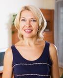 Mulher madura de sorriso na casa ou no escritório Foto de Stock
