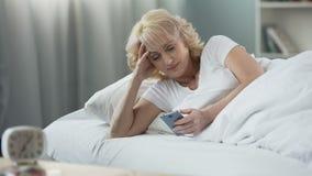 Mulher madura de sorriso que encontra-se na cama e em verificar o email no smartphone, manhã filme
