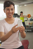 Mulher madura de sorriso que usa seu telemóvel no gym, olhando a câmera Foto de Stock Royalty Free