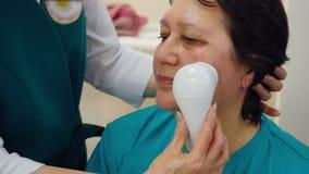 Mulher madura do retrato que recebe a massagem de cara com o massager na clínica da cosmetologia filme