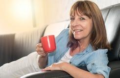 Mulher madura durante a ruptura de café em casa, efeito da luz foto de stock royalty free