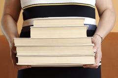 Mulher madura ereta que guarda uma pilha de livros fotografia de stock
