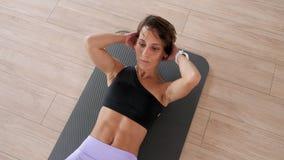 A mulher madura está fazendo o exercício da trituração do Abs lentamente na esteira no gym vídeos de arquivo