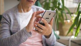 A mulher madura está guardando o smartphone, música de escuta vídeos de arquivo