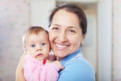 Mulher madura feliz com bebê Foto de Stock