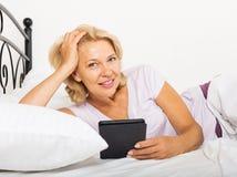 Mulher madura feliz com livro eletrônico Foto de Stock Royalty Free