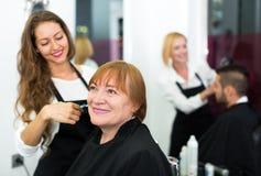 A mulher madura feliz corta o cabelo Foto de Stock Royalty Free
