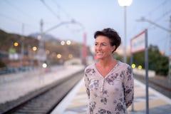 Mulher madura feliz do turista que pensa ao esperar o trem foto de stock