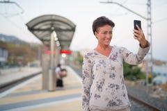 Mulher madura feliz do turista que toma Selfie no estação de caminhos de ferro foto de stock