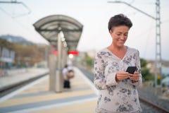 Mulher madura feliz do turista que usa o telefone no estação de caminhos de ferro foto de stock royalty free