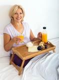 Mulher madura feliz que aprecia o café da manhã Imagem de Stock Royalty Free