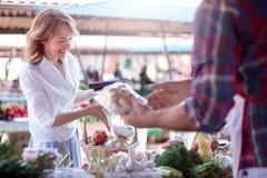 Mulher madura feliz que compra vegetais orgânicos frescos em um mercado local fotografia de stock royalty free