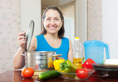 Mulher madura feliz que cozinha o almoço Foto de Stock