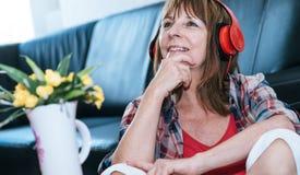 Mulher madura feliz que escuta a música foto de stock royalty free