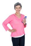 Mulher madura feliz que guarda a garrafa quando música de escuta Foto de Stock Royalty Free