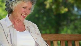 Mulher madura feliz que lê uma novela vídeos de arquivo