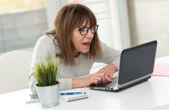 Mulher madura feliz que tem uma boa surpresa no portátil fotos de stock