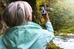 Mulher madura idosa atrativa agrad?vel com o cabelo cinzento brilhante que toma as fotos e os selfies exteriores fotografia de stock royalty free