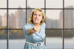 Mulher madura irritada que aponta para a frente Imagens de Stock