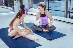 Mulher madura jovial que trai segredos com instrutor da ioga foto de stock