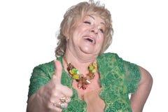 Mulher madura lindo que veste o polegar verde da exibi??o do vestido isolado acima foto de stock royalty free