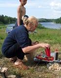 Mulher madura loura bonito que prepara a salada vegetal na campanha imagens de stock royalty free