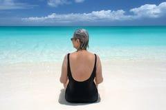 Mulher madura na praia, nos turcos e no caicos Foto de Stock