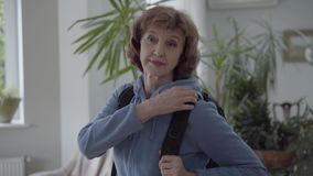 Mulher madura na trouxa confortável do preto hoody azul da fixação em sua parte traseira filme