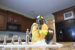 Mulher madura no potenciômetro de lavagem do terno da esteira de Haz na banca da cozinha Fotos de Stock