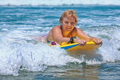 Mulher madura positiva que surfa com divertimento em ondas de oceano fotos de stock
