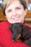 A mulher madura prende o cão Fotografia de Stock Royalty Free