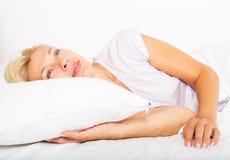 Mulher madura que acorda na cama Fotografia de Stock Royalty Free