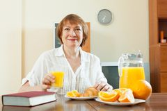 Mulher madura que come o café da manhã com livro Fotos de Stock Royalty Free