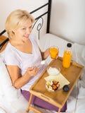 Mulher madura que come o pequeno almoço Fotos de Stock Royalty Free