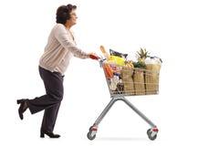 A mulher madura que corre e que empurra um carrinho de compras encheu-se com o gro fotografia de stock