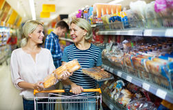 Mulher madura que escolhe a pastelaria no supermercado Foto de Stock