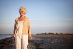Mulher madura que está na praia Fotografia de Stock