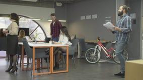 Mulher madura que fala com seu colega à moda novo no escritório No fundo o homem novo põe sua bicicleta perto do vídeos de arquivo