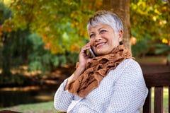 Mulher madura que fala no telefone celular no parque foto de stock royalty free