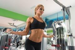 Mulher madura que faz o exercício do bíceps na máquina do cabo foto de stock