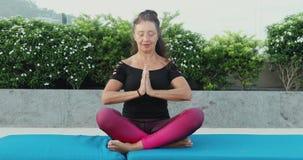 Mulher madura que faz a posição da ioga dos lótus fora no jardim filme