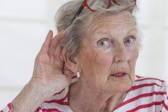 Mulher madura que guarda a mão à orelha fotos de stock royalty free