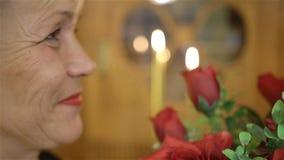 Mulher madura que guarda um grande ramalhete de rosas vermelhas e do sorriso Aniversário, dia de mães, aniversário ou Valentim video estoque