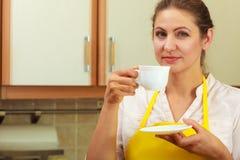 Mulher madura que guarda a xícara de café na cozinha Fotos de Stock